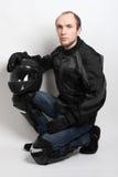 Man sitting and holding helmet in studio Stock Photos