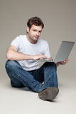 Man sitting and holding laptop Royalty Free Stock Photos