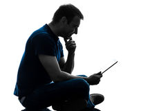 Man sitting holding watching digital tablet  silhouette. One  man sitting holding digital tablet in silhouette on white background Royalty Free Stock Photography