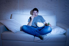 Man sitting at home sofa in living room watching movie or sport in tv eating popcorn and drinking beer. Young man sitting at home sofa in living room watching Stock Photography