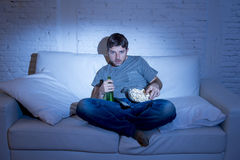 Man sitting at home sofa in living room watching movie or sport in tv eating popcorn and drinking beer Royalty Free Stock Photography