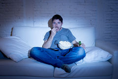 Man sitting at home sofa in living room watching movie or sport in tv eating popcorn and drinking beer Stock Image