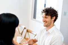 Portrait of man sitting and talking to woman indoors Royalty Free Stock Images