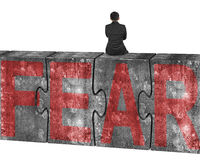 Man sitting on huge concrete puzzles with red fear word Royalty Free Stock Photo