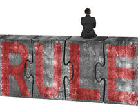 Man sitting on huge concrete puzzles with red rule word Stock Photo