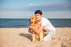 Man sitting and hugging his dog on the beach Royalty Free Stock Images