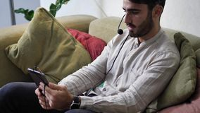Man sitting indoors video chatting with tablet PC. Handsome young man sitting indoors video chatting with tablet PC and headset, smiling for the camera stock footage