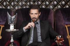 Man sitting and inhaling shisha in restaurant. Royalty Free Stock Photos