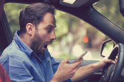 Man sitting inside car with mobile phone texting while driving. Man sitting inside car with mobile phone in hand texting while driving. Shocked guy checking his royalty free stock image