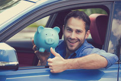 Man sitting inside new car holding piggy bank showing thumbs up Royalty Free Stock Image