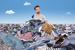 Man in a mess of laundry. A man is sitting inside a pile of clothing. The area around him is covered in clothing Royalty Free Stock Photo