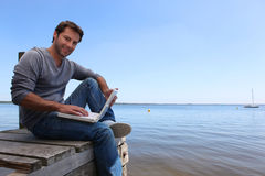 Man sitting on a jetty Stock Image