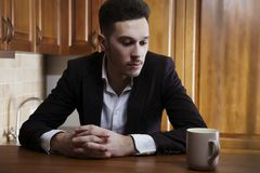 Man sitting at the kitchen counter Royalty Free Stock Images