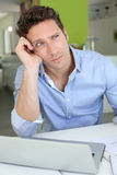 Man sitting in kitchen with a displeased look Stock Photography