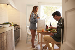 Man sitting in kitchen while his girlfriend unpacks shopping Royalty Free Stock Photos