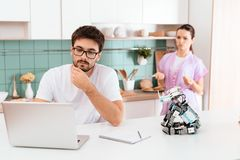A man is sitting at the kitchen table and programming a robot. The robot is on the table. Behind the woman. A men is sitting at the kitchen table and Stock Image