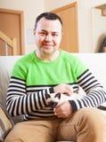 Man sitting with kitten. Joyful man sitting on couch with kitten royalty free stock image