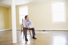 Man sitting on ladder in empty space holding paper Stock Photos