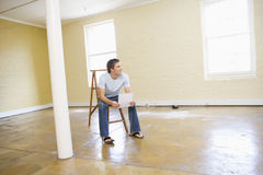 Man sitting on ladder in empty space holding paper Royalty Free Stock Photography