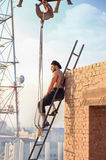 Man sitting on ladder on high. Royalty Free Stock Photo