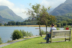 Man sitting by a lake. Stock Photo