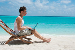 Man sitting with laptop on the beach Royalty Free Stock Photos