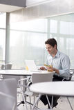 A man sitting at a laptop eating a sandwich Stock Photography