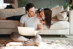 Man sitting with laptop and his woman at home Royalty Free Stock Photography
