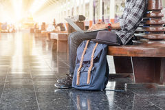 Man sitting with laptop. travel bag at the train station. Stock Photo