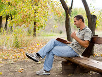 Man sitting laughing and reading Royalty Free Stock Image