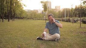 A man sitting on the lawn in a green Park on a summer day at sunset drinking a drink and talking on the phone stock video