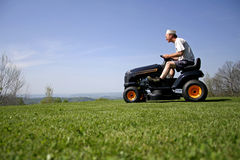 Man sitting on a lawnmower Stock Photos
