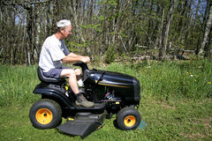 Man sitting on a lawnmower stock images