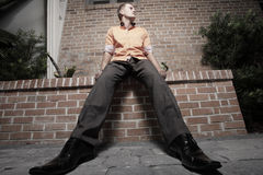 Man sitting on a ledge Stock Images