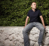 Man sitting on a ledge. Young man sitting on a ledge by bushes stock photo