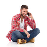 Man sitting with legs crossed and talking on the phone Royalty Free Stock Image