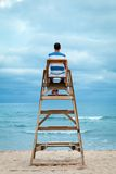 Man sitting on lifeguard chair. Outdoor stock photography