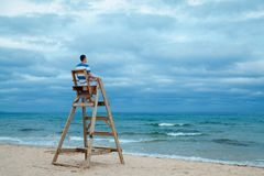Man sitting on lifeguard chair. Outdoor stock photos