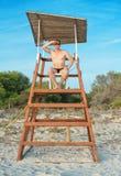 Man sitting on lifeguard tower. Royalty Free Stock Photos