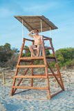 Man sitting on lifeguard tower. stock photography
