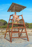 Man sitting on lifeguard tower. Royalty Free Stock Image