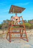 Man sitting on lifeguard tower. Royalty Free Stock Photo
