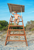 Man sitting on lifeguard tower. Stock Photo