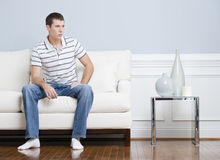 Man Sitting on Living Room Couch Stock Image