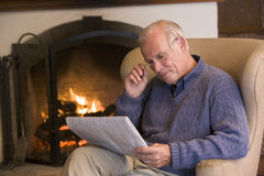 Man sitting in living room by fireplace Royalty Free Stock Image
