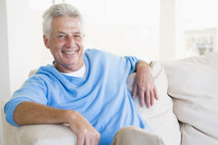 Man sitting in living room smiling Stock Photo