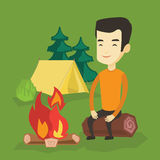 Man sitting on log near campfire in the camping. Stock Images