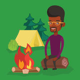 Man sitting on log near campfire in the camping. Royalty Free Stock Photo