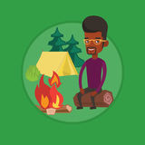 Man sitting on log near campfire in the camping. Stock Photography