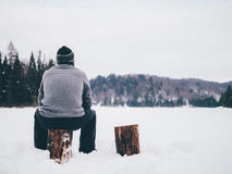 Man sitting on log in snow  Stock Image